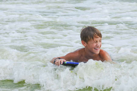 child boy: Happy cute kid on a boogie board in the ocean water with copy space. Stock Photo