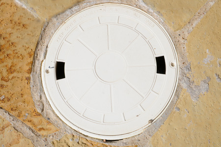 skimmer: The lid to a swimming pool skimmer on flagstone.