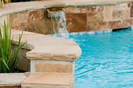 Beautiful swimming pool with flagstone wall that has waterfall pouring out of it. Stockfoto
