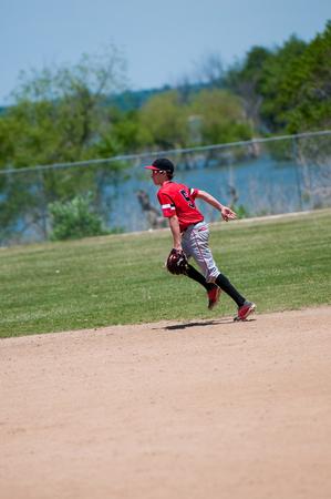 shortstop: American youth baseball player running on field.