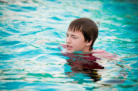 puckered lips: Handsome and silly teen boy with braces making mouth puckered in swimming pool