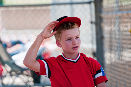 baseball dugout: Teenage baseball boy in dugout reaching for ball cap.