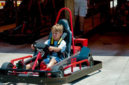 carting: Adorable young kid on a go cart at an amusement park racing.