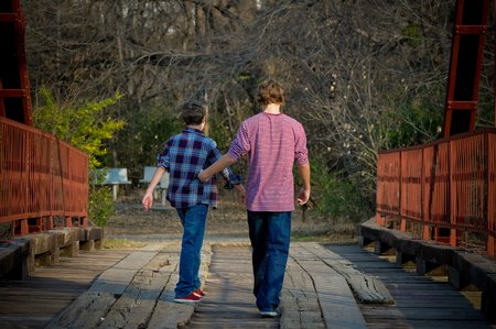 people from behind: Two boys from behind walking on an old bridge.