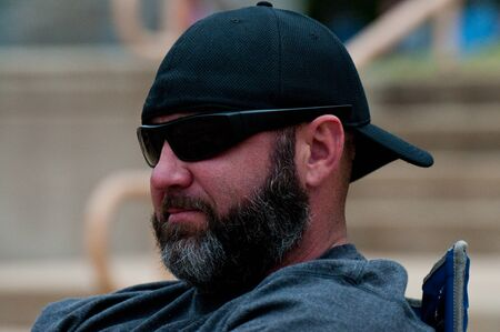 Middle-aged man with black and grey beard wearing sunglasses and hat backwards.