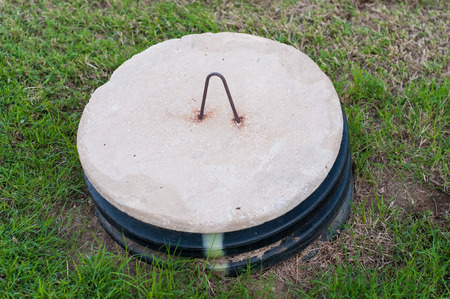 Close up of concrete septic system lid in green grass.