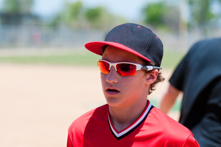 Youth baseball boy up close running of field with sunglasses and hat. Stock Photo