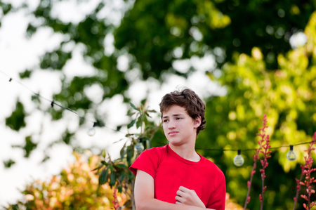 blank expression: Handsome teenage boy outside looking sideways with blank expression on face. Stock Photo