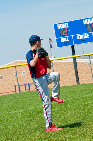 American baseball boy pitching with scoreboard in background.