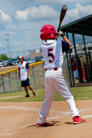 Young baseball player at home plate about to bat.