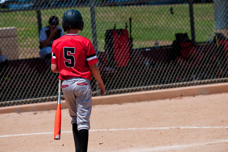 dugout: Rear view of american baseball boy going up to bat.