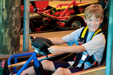 go: Adorable happy young kid on a go cart at an amusement park looking sideways.