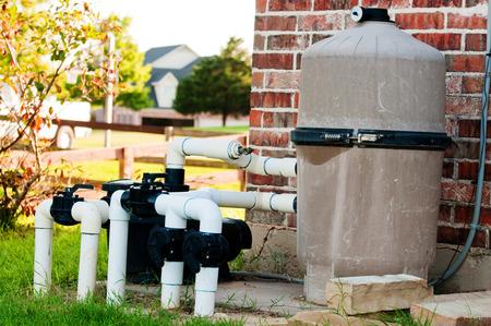 Swimming pool pump system next to red brick wall. Standard-Bild