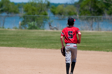 American youth baseball player running on field.