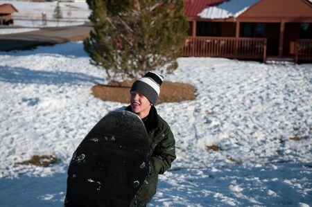 toboggan: Young boy with toboggan happy carrying a sled. Stock Photo