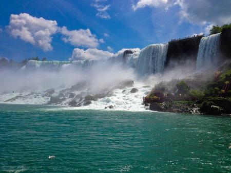 water fall: Beautiful Niagara Falls from on a boat with tourist wearing rain jackets.