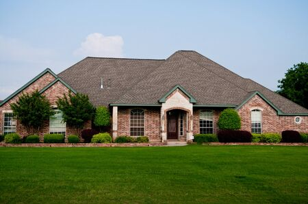 suburban: Red brick home in a residential neighborhood with beautiful green grass and landscaping.