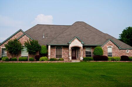 Roter Ziegelsteinhaus in einer Wohngegend mit schönem grünem Gras und Landschaftsbau. Standard-Bild