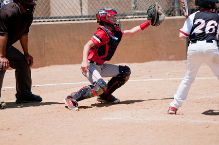 Baseball catcher reaching to catch a wild pitch with umpire behind him. Stock fotó - 58931203