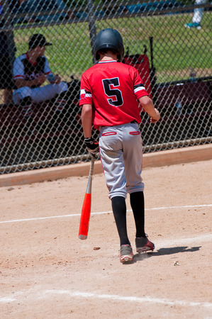 Rear view of american youth baseball boy going up to bat. Stock Photo