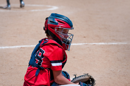 baseball catcher: American youth baseball catcher looking at coach for signals.