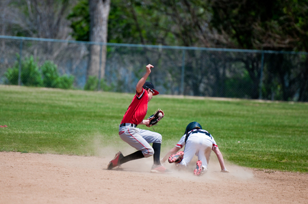 Baseball shortstop tagging a player out at second base that was sliding.