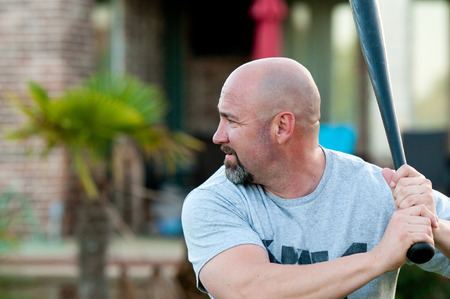 baseball swing: Middle-aged bald man playing holding baseball bat ready to swing. Stock Photo