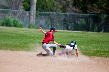 Baseball shortstop tagging out a player sliding at second base. Stock Photo