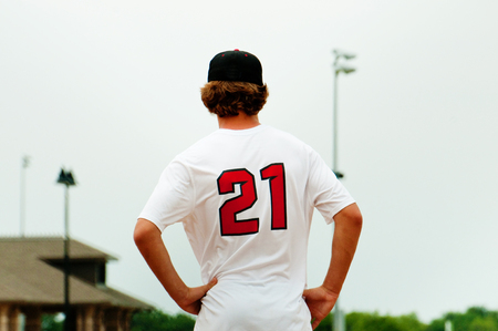 sports clothing: Baseball player from behind with hands on hip.
