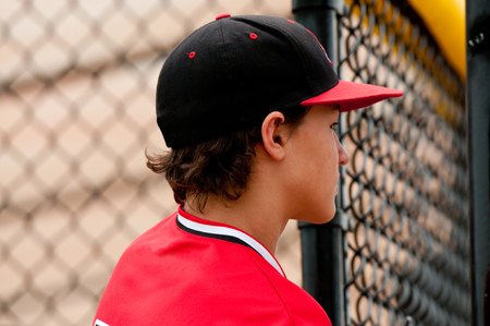 Profile of American baseball player close up in the dugout.
