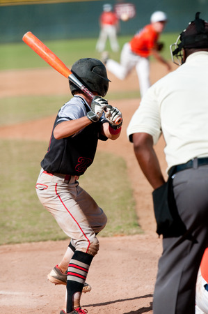 umpire: Teenage boy batting with umpire behind him.