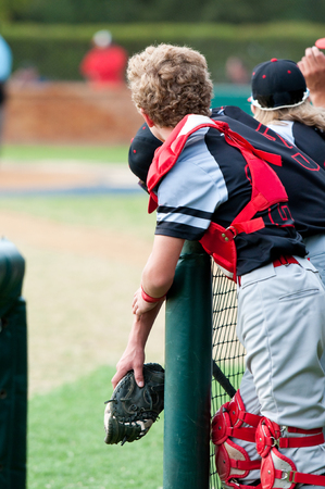Youth baseball team and catcher standing in the dugout watching the game. Stock Photo