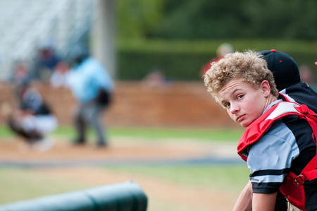 baseball dugout: Baseball boy looking at camera during the game with copy space.