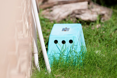 Blue septic control box outdoors next to home. Stock Photo