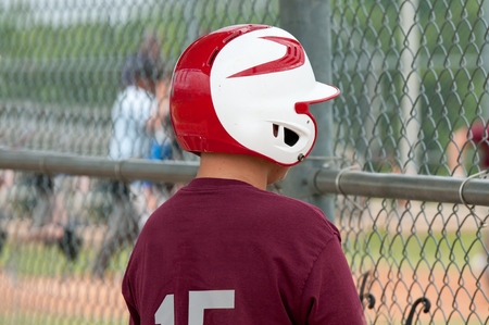 Little league baseball boy looking through dugout fence with red helmet.