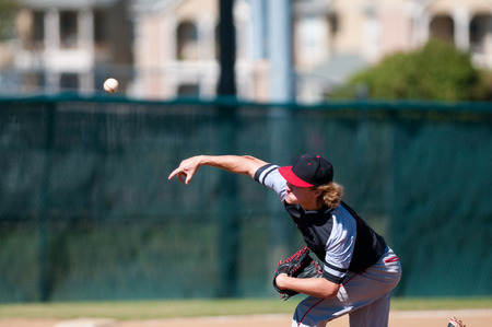 baseball pitcher: American teenage high school pitcher on the mound during a game.