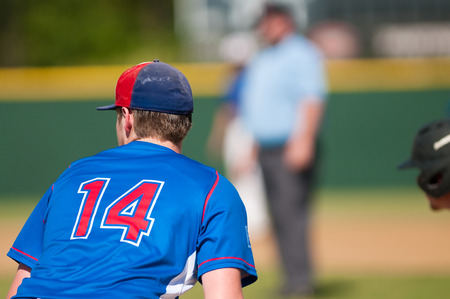 14: High school baseball player from behind.