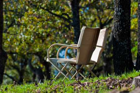 patio chairs: Set of two old yellow metal patio chairs outdoors next to tree at a park. Stock Photo