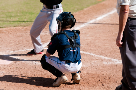 baseball catcher: Youth american baseball catcher and umpire behind home plate during a game.