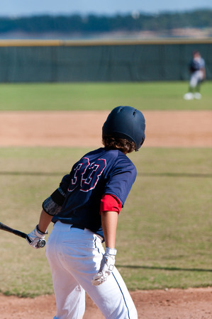 Young kid about to swing the bat, wearing a blue jersey and helmet.