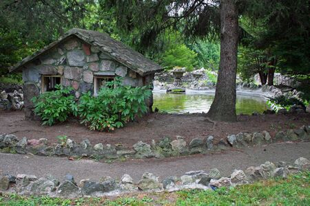 Old Rock House overlooking a serene pond Stock Photo