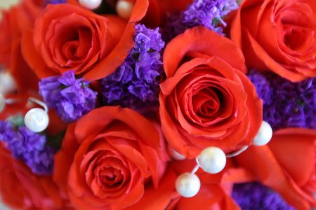 A bouquet of red roses and purple flowers