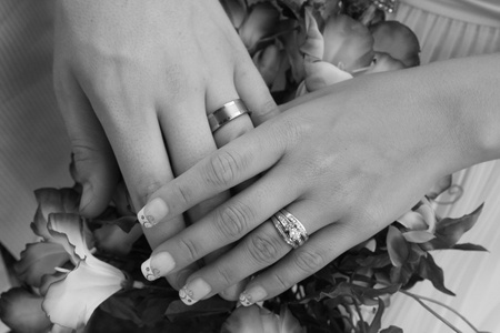 Holding hands with wedding bands in black and white photo