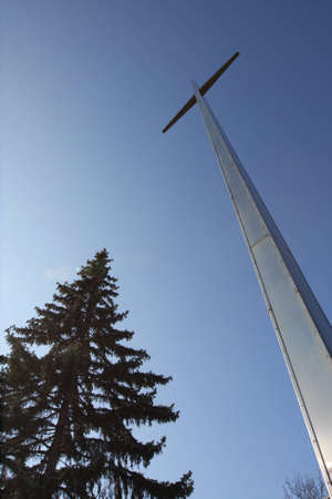 Tall Cross and Pine Tree leaning to one another.