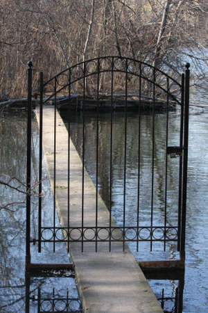 A lonely gate entrance  over the water. Stock Photo