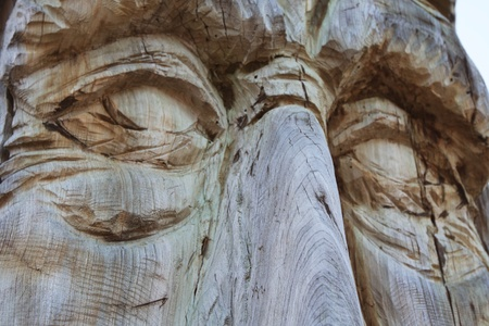 A wooden totem pole close-up of the eyes.