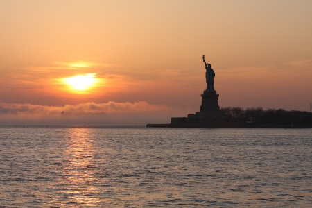 A sunset nearing the Statue of Liberty at dusk. Stock Photo