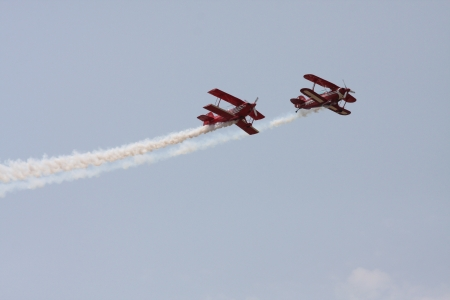 Two red Bi-planes flying close with smoke streaming