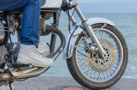 singly: Someone on old motorcycle parking at the seaside in evening