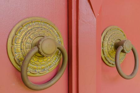 Old golden knob installed on big red wood door photo